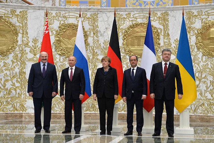 Photo: At a summit in Minsk on 11 February 2015, the leaders of Belarus, Russia, Germany, France, and Ukraine agreed to a package of measures to alleviate the ongoing war in the Donbass region of Ukraine. The talks that led to the deal, overseen by the Organization for Security and Co-operation in Europe (OSCE), were organised in response to the collapse of the Minsk Protocol ceasefire in January–February 2015. Credit: Wikimedia Commons.
