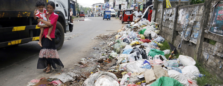 Photo: Hekitta: Pedestrians are forced to walk on the middle of the road because the garbage has taken over the pavement. Source: The Sunday Times | M.A. Pushpa Kumara